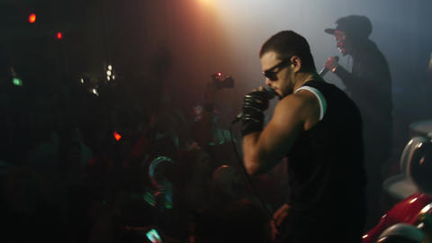 Rap artists perform on stage at Halloween party in crowded nightclub Footage