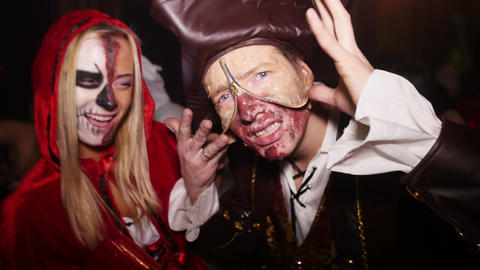Girl as scary Red Riding Hood, man as pirate with bonded skin at Halloween party Footage