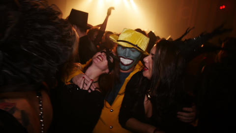 Man as Stanley Ipkiss from Mask movie among girls in masks at Halloween party Footage