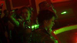 Two girls in vintage look with hats dance at Halloween party in nightclub. Laser Footage
