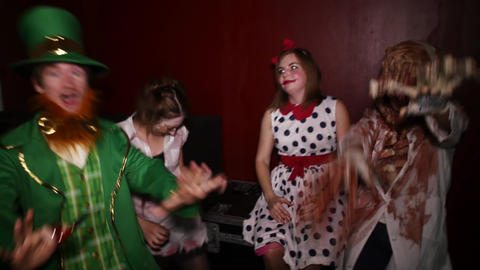 People in costumes have fun at Halloween party in club. Doll, octopus, green man Live Action