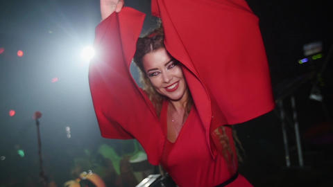 Girl in red bat costume covers by wings at Halloween party. Slow motion Footage
