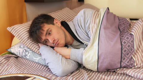 Young Man Lying, Looking And Thinking In Bed stock footage