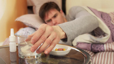 Sick man taking pill while lying on bed Live Action