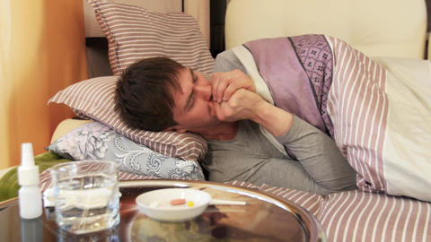 Sick Man Lying On Bed And Coughing stock footage