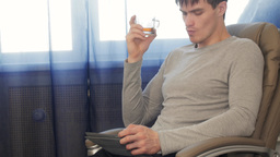 Man with tablet pc sitting on chair, drinking tea Footage