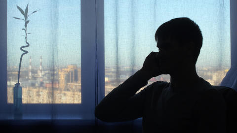 Silhouette man, talking at window background Footage