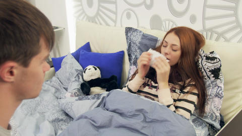 Husband takes temperature at sick wife in bed Footage