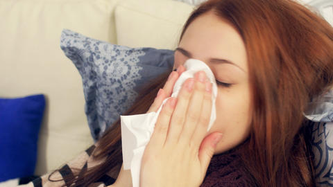 Sick woman in bed blowing nose in paper tissue Footage