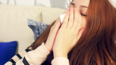 Sick woman in bed sneezing in paper tissue Footage