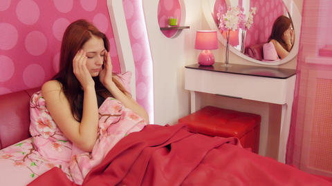 Redhead woman in pink bed suffering headache Footage