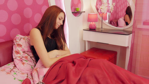 Woman with menstrual pain laying in pink bed Footage