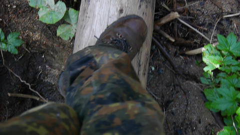 Soldier goes on a tree trunk shot down in the woods 86a Footage