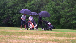 three golf player walking with caddies through the rain Footage