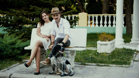 young man and woman sitting on a bench where a man stroking a dog Footage