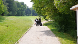 two men in a golf car driving behind walking people Footage