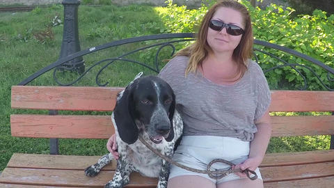 Woman With A Dog Sitting On A Bench In The Park stock footage