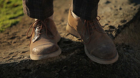 legs in men's boots are on the ground Footage