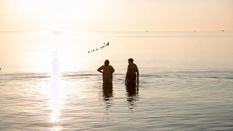 Two Elderly Women Go Swimming At Sunrise stock footage