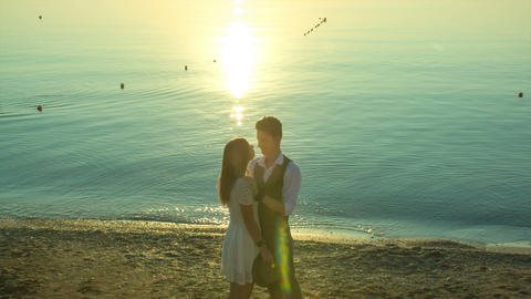 man embracing a woman on the beach at sunrise Footage