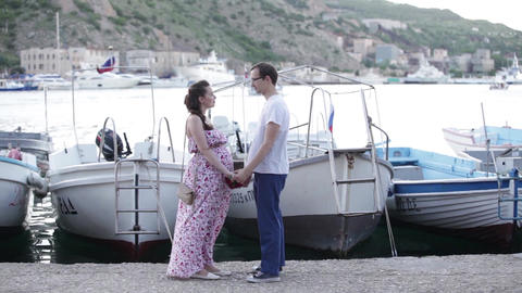 Pregnant wife and her husband hold hands on a background of boats Live Action