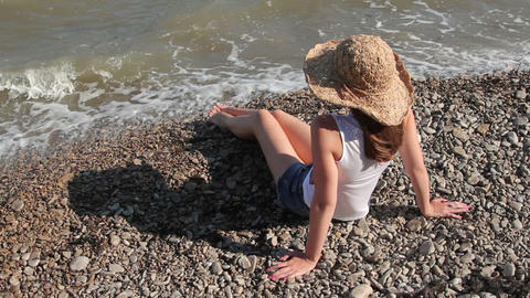 woman in a hat sitting on the seashore Footage