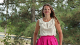 young woman in a pink dress on the background of fir trees Footage