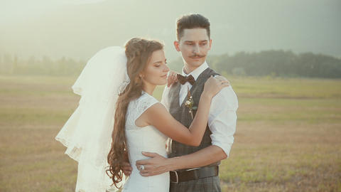 bride and groom embracing each other on a walk in the countryside at sunset Live Action