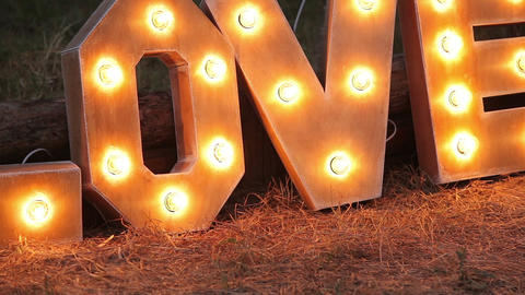 Word love consisting of the letters highlighted with bulbs on lawn at night Live Action