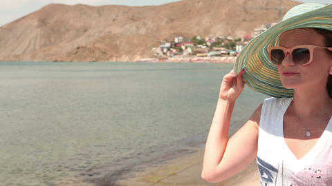 young woman in sunglasses and hat on a background of mountains and sea city Footage