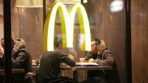 People sit at little tables at McDonald's restaurant Footage
