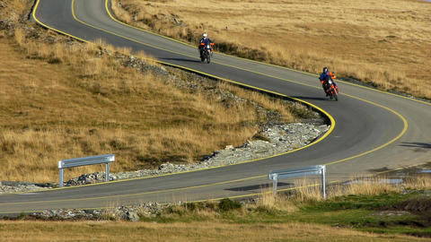 Bikers descend on a road serpentines among other vehicles 117a Live Action
