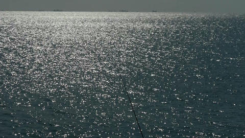 Sparkling water surface and fishing rod,horizon,skyline Footage