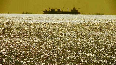 Sparkling water surface and Vessel Ship,horizon,skyline,gold Footage