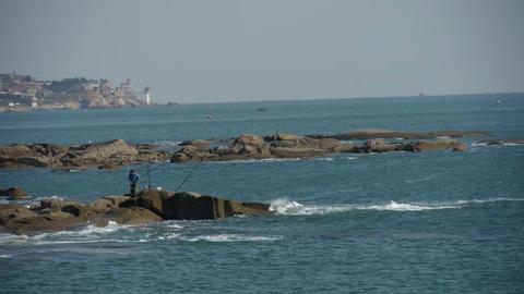 fishing people on Beach Reef,Sea spray Stock Video Footage