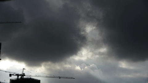 Dark clouds cover sky,Cranes,building high-rise,House silhouette Footage