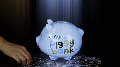 Piggy bank coin drop in black space,Piggy Bank Savings RMB and rays lights Footage