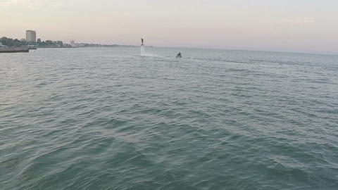 People Flying Over The Sea In The Water Column stock footage