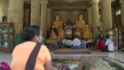 Shwedagon Pagoda, people praying to Buddha statues Footage