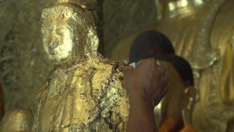 Shwedagon Pagoda, worshiper paste gold buddha Footage