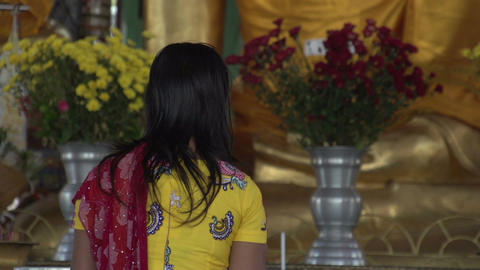 Shwedagon Pagoda, woman praying to Buddha statue Footage