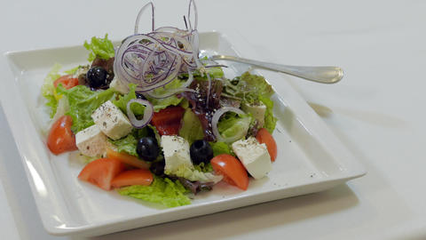 Waiter Puts A Plate With Greek Salad On A Table HD Footage