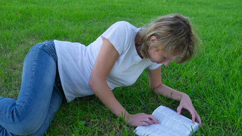 Attractive girl lying on the grass and reading a book Footage