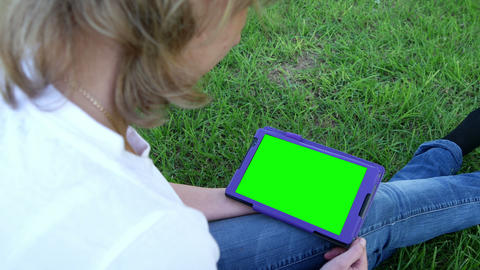 Attractive girl sitting on the grass with tablet computer Footage