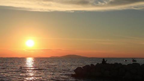 Perfect sea sunset, man fishing on jetty, beautiful nature Footage