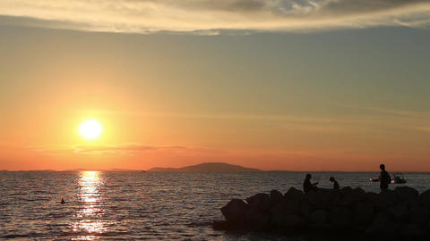 Perfect sea sunset, man fishing on jetty, family joins him, beautiful nature Footage