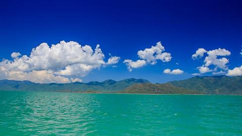 gleams of azure sea against distant islands sky cumulus clouds Footage