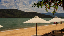 white sunshade parasols on sand beach at azure sea Footage