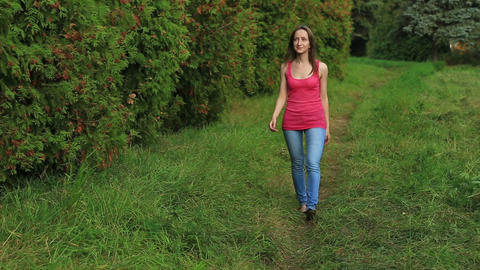 Girl walking away through green alley Footage
