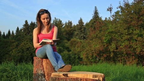Young woman sitting in a park put on sun glasses and reading a book Footage